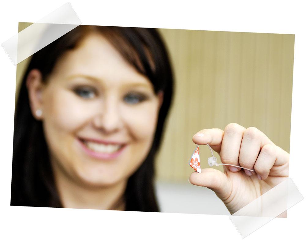 Frau zeigt Hörgerät